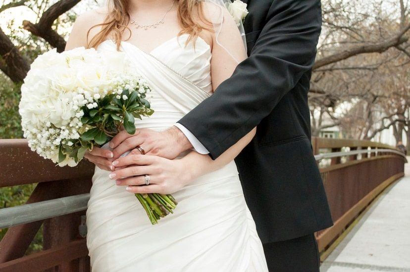 Couple holding hands with flower bouquet