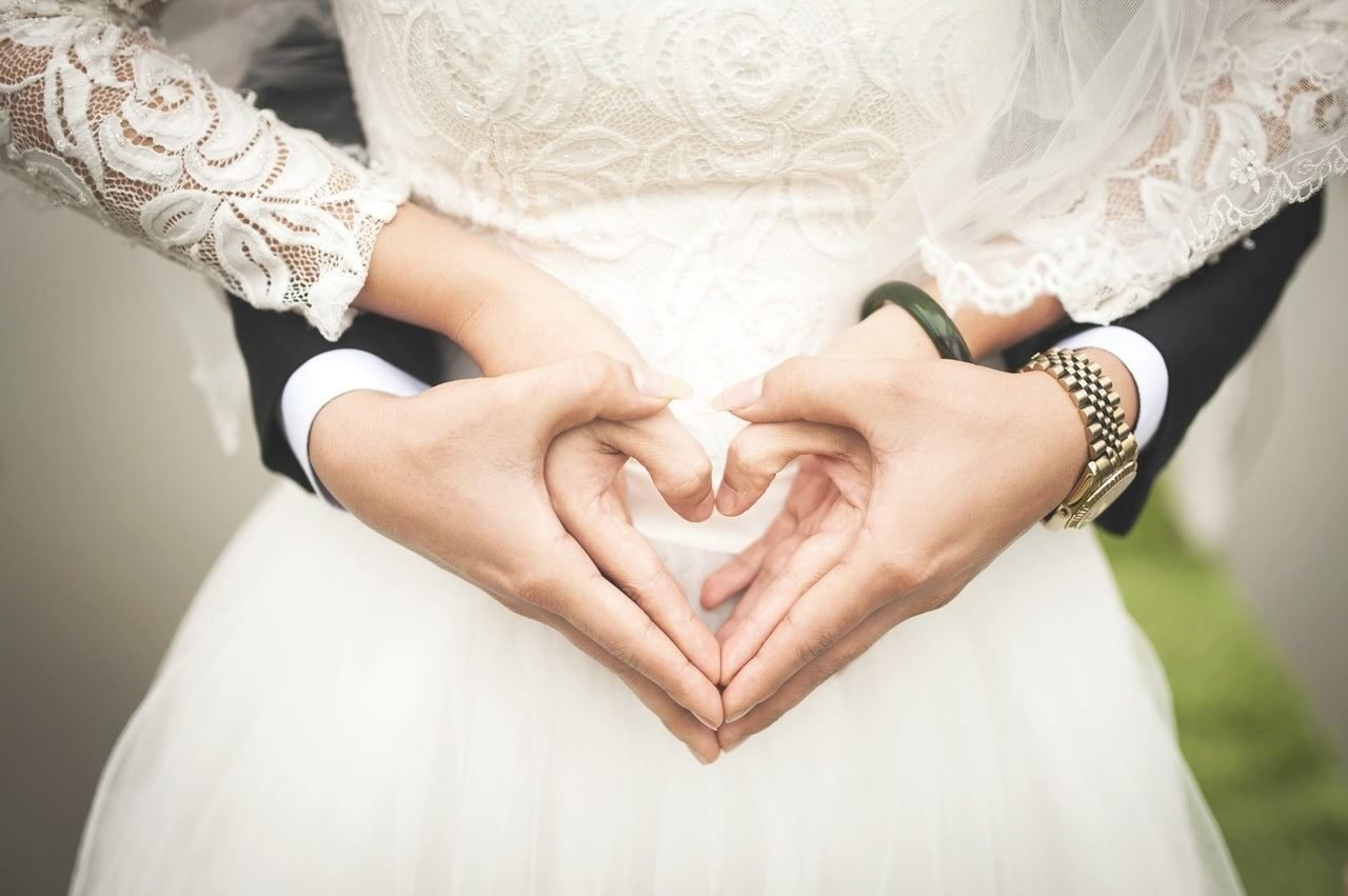 Couple on their wedding day holding hands love heart bride groom DIY vs Professional Service