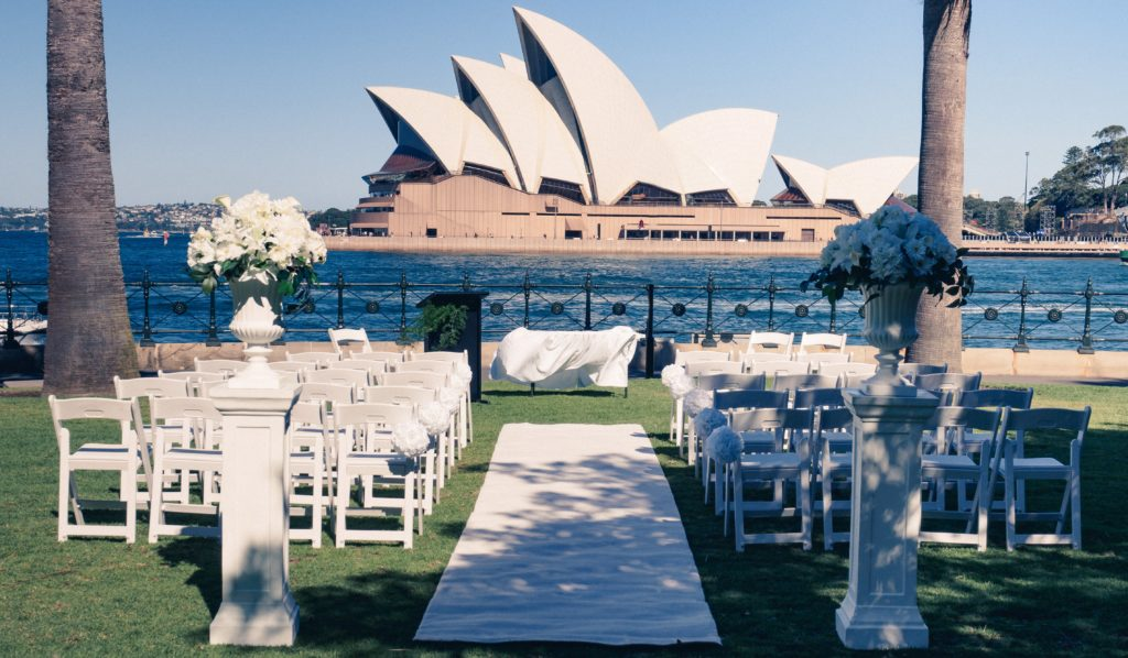 Sydney Destination Wedding Australia: Opera House Ceremony Setup overlooking harbour CBD White Pillars Carpet Blue Sky