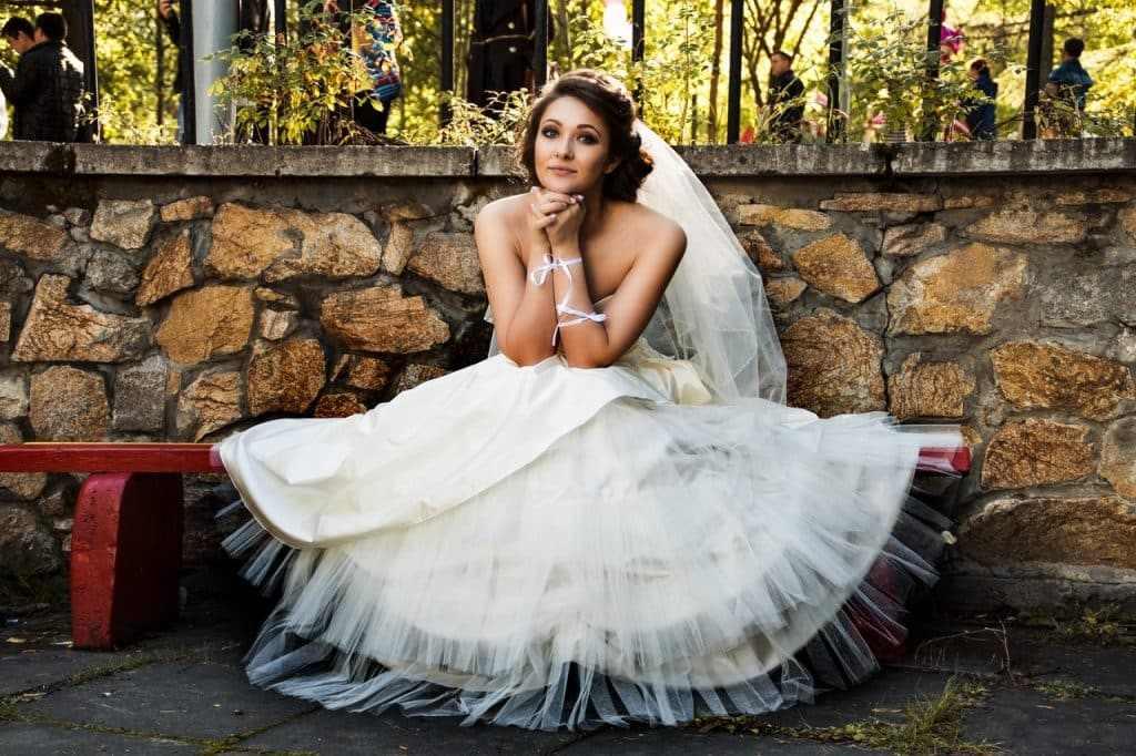 Bride White wedding dress sitting outside thinking why consider wedding planner or coordinator
