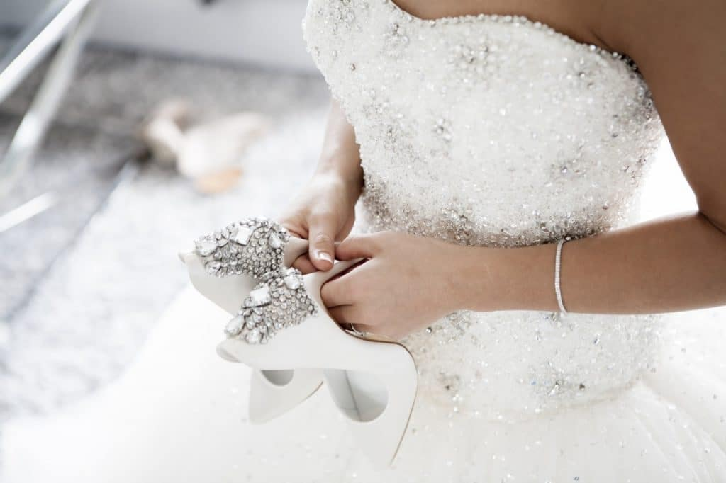 Bride holding wedding shoes white silver
