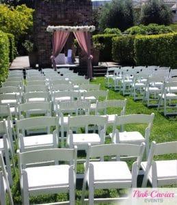 garden wedding ceremony white chairs pink arch WM