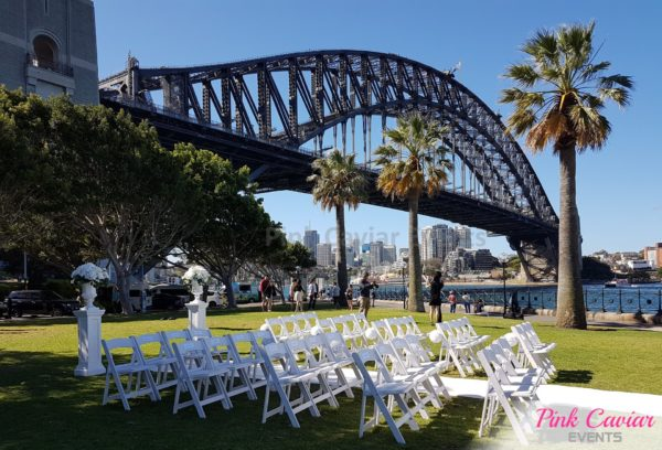 outdoor wedding ceremony sydney harbour bridge white chairs sunny day
