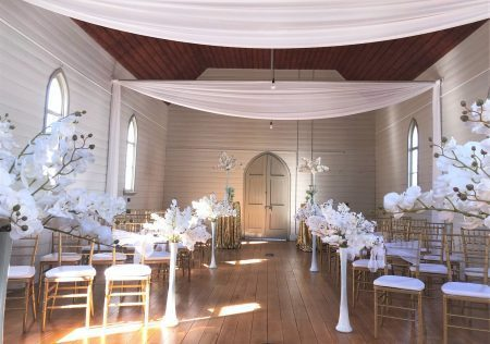 White Orchids in tall vases for wedding ceremony set up